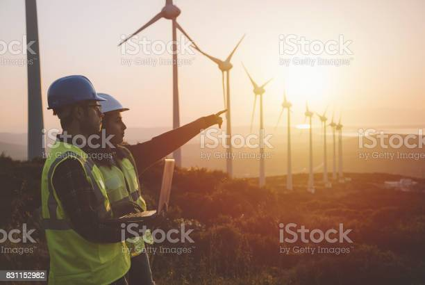 Young Maintenance Engineer Team Working In Wind Turbine Farm At Sunset Stock Photo - Download Image Now