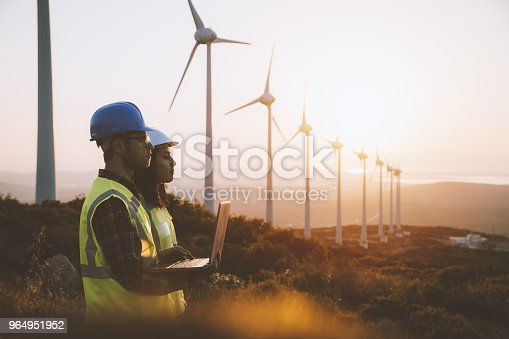 Young electrical engineer woman and business man standing in front of wind turbines checking and working about technical problems and writes the results of measurements with laptop pc in wind power plant electric energy station. xxxl size taken with canon 5d mIV
