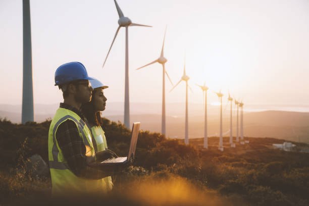 Young maintenance engineer team working in wind turbine farm at sunset stock photo