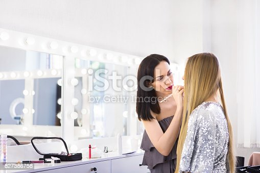 istock Young makeup artist doing makeover to pretty model 827386758