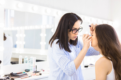 Young makeup artist doing makeover to pretty model