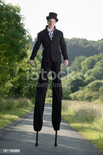 Young artist walking on stilts. With a black suit. Taken in morning time with backlit.