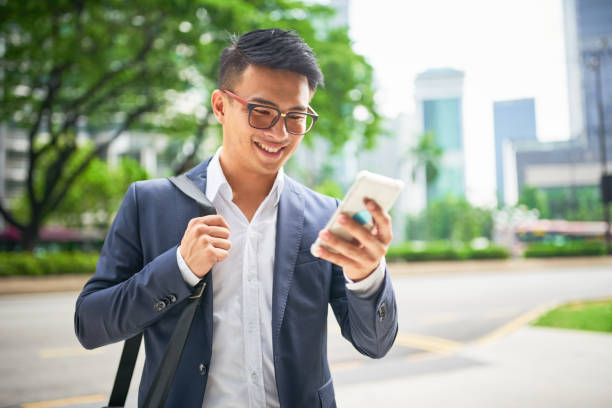 Young malaysian businessman on smart phone Young malaysian businessman in the streets of downtown Kuala Lumpur smiling while looking to his his smart phone for a crowed sourced taxi to arrive . Kuala Lumpur, Malaysia, Asia southeast asian ethnicity stock pictures, royalty-free photos & images
