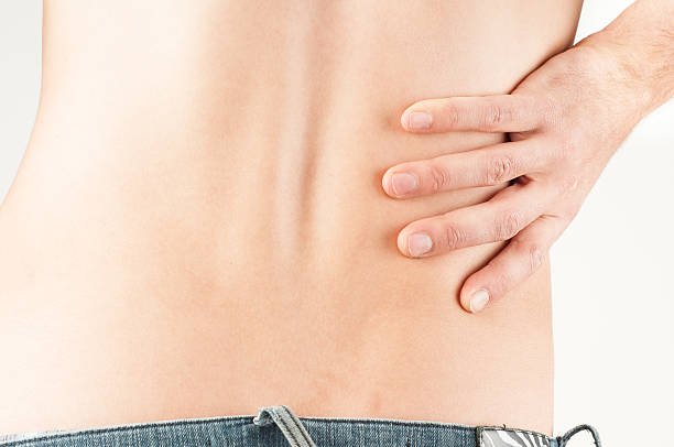 Young male adult with back pain stock photo