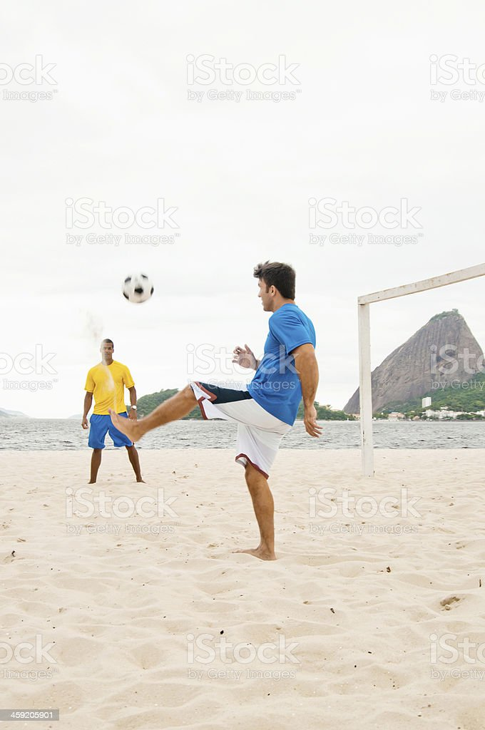 Young Male Adults Playing Football on Praia do Flamengo Beach stock photo