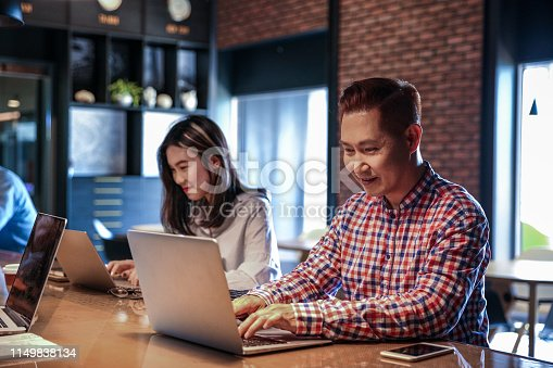 istock Young male and coworker working with computer 1149838134