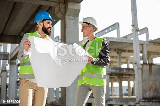 681242254 istock photo Young male and female architects or business partners looking at floor plans on a construction site 946679206