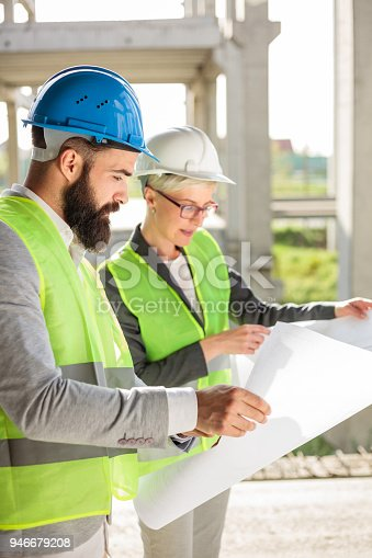 681242254 istock photo Young male and female architects or business partners looking at floor plans on a construction site 946679208