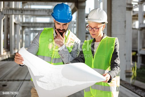 681242254 istock photo Young male and female architects or business partners looking at floor plans on a construction site 946679250