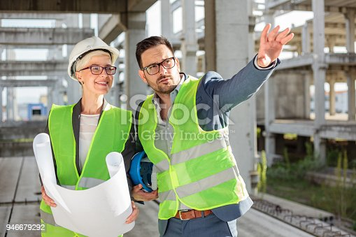 681242254 istock photo Young male and female architects or business partners looking at floor plans on a construction site 946679292