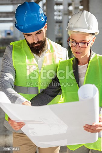 681242254 istock photo Young male and female architects or business partners looking at floor plans on a construction site 946679314