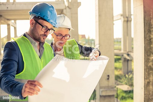 istock Young male and female architects or business partners looking at floor plans on a construction site 946679316