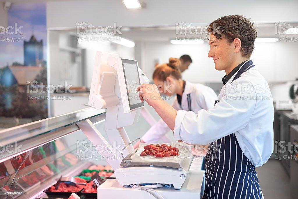Young Male And Female Butchers Working In A Butchers Shop