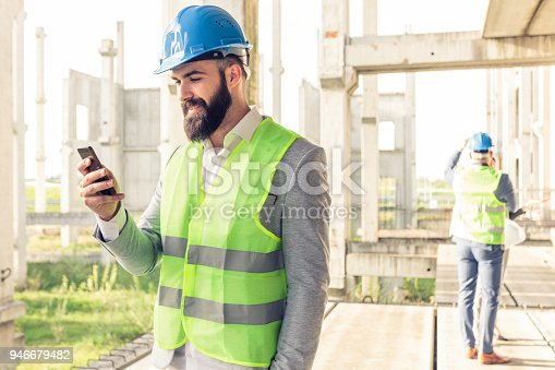 1166176793 istock photo Young male architect or businessman using a smartphone on a construction site. 946679482