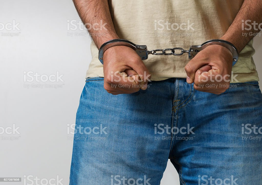 Young male arrested with handcuffs stock photo