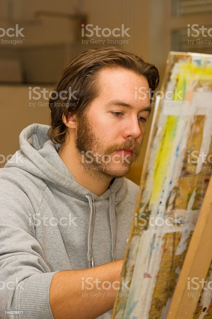A young male artist drawing at an easel royalty-free stock photo