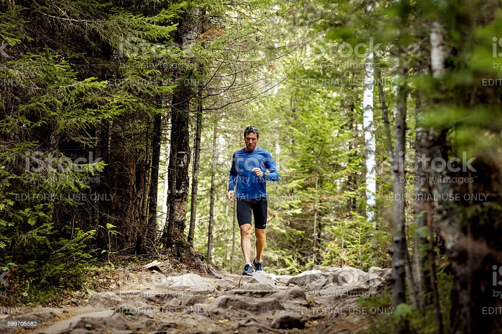 young male athlete active runs rocks trail in woods stock photo
