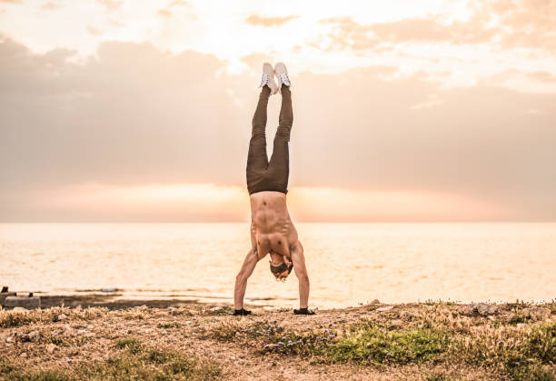 Young male athlete doing a hand stand outdoors by the sea. stock photo