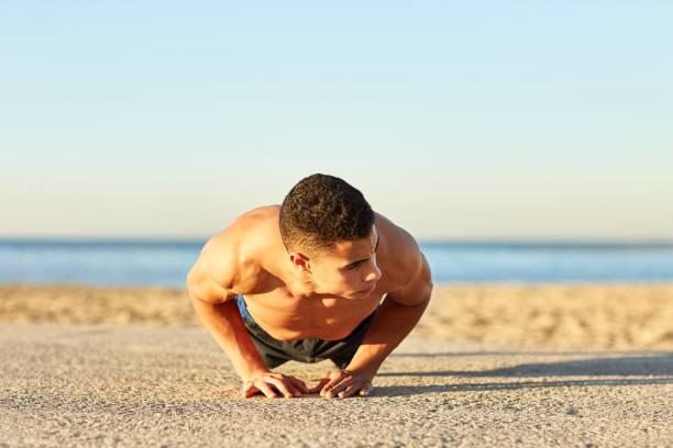 Young male athlete doing diamond push-ups at beach stock photo