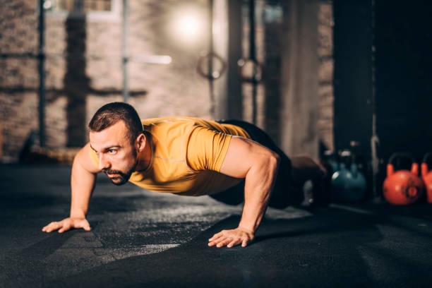 Young male athlete doing push ups workout in a gym gym stock photo