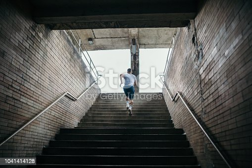 Young male athlete running up the stairs