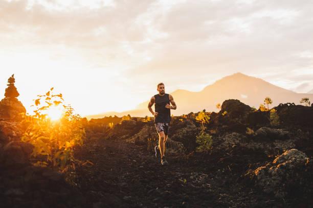 unga manliga idrottare trail körs i bergen vid sol uppgången. fantastiskt svart lava vulkaniskt landskap av bali på bakgrund. äventyrs sport koncept. - jogging hill bildbanksfoton och bilder