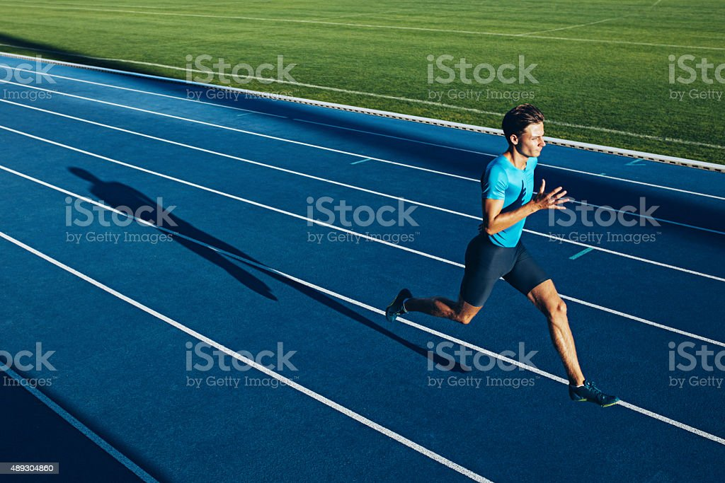 Young male athlete training on a race track stock photo