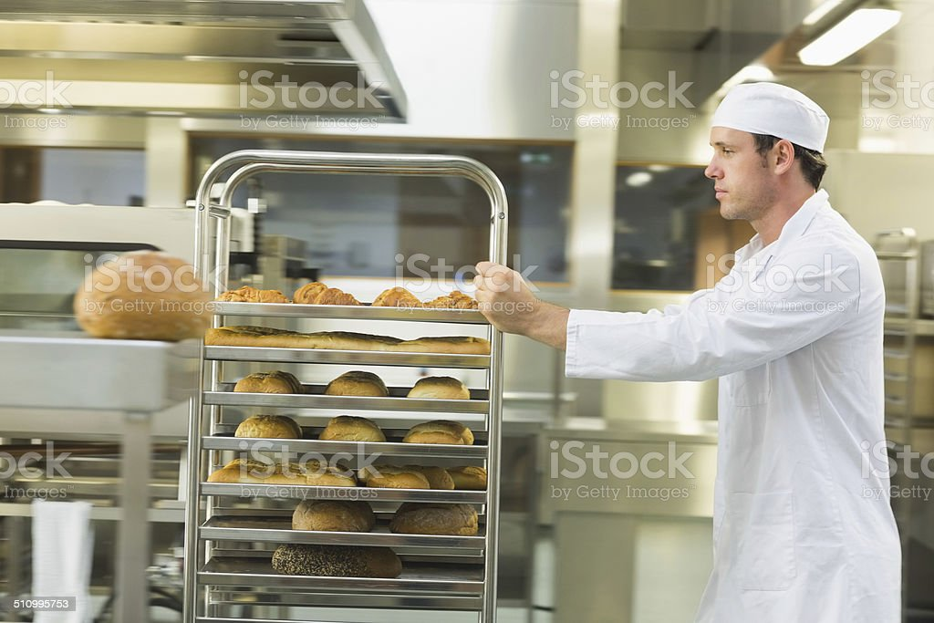 Young male baker pushing a trolley stock photo