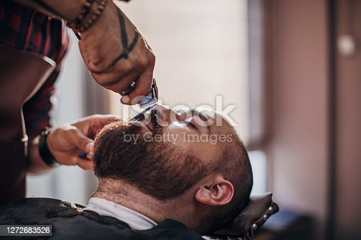 Young bearded man getting beard haircut by young male hairdresser while lying in chair in a barber shop.