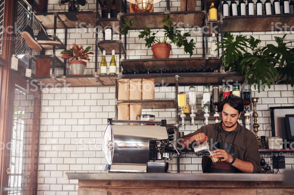 Young male barista making a cup of coffee stock photo