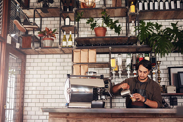 young male barista making a cup of coffee - barista stock photos and pictures