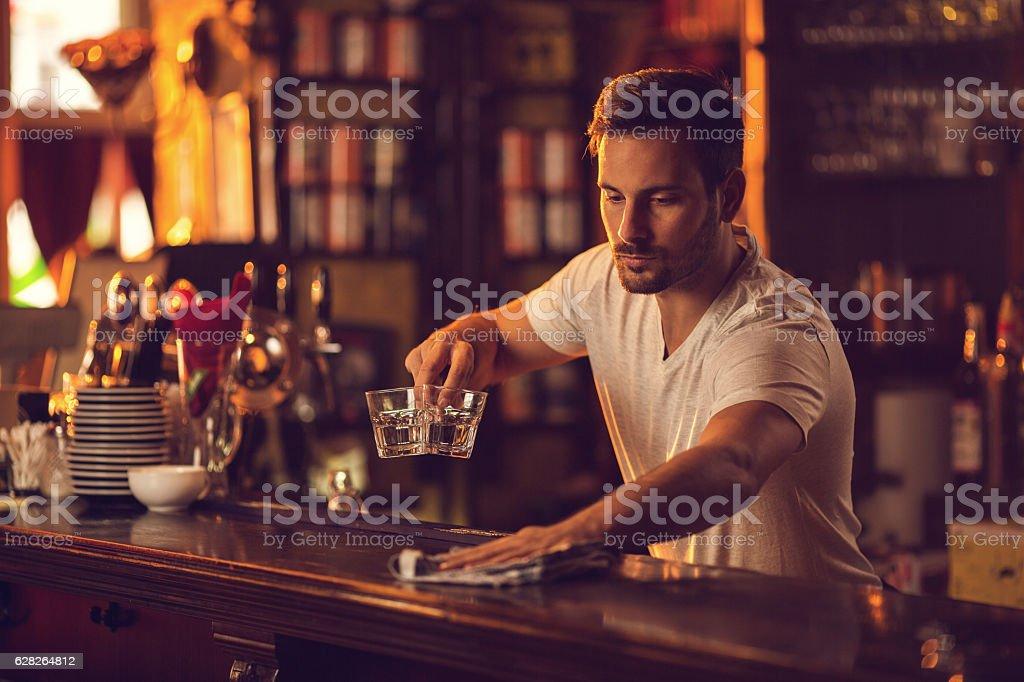 Young male bartender cleaning bar counter after work. stock photo