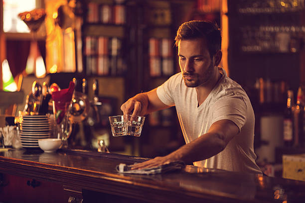 young male bartender cleaning bar counter after work. - barman photos et images de collection