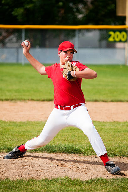 Young Male Baseball Pitcher Stretches on Pitcher's Mound A 12 year old boy pitches from mound.  (Logo design has property release from creator.) infield stock pictures, royalty-free photos & images