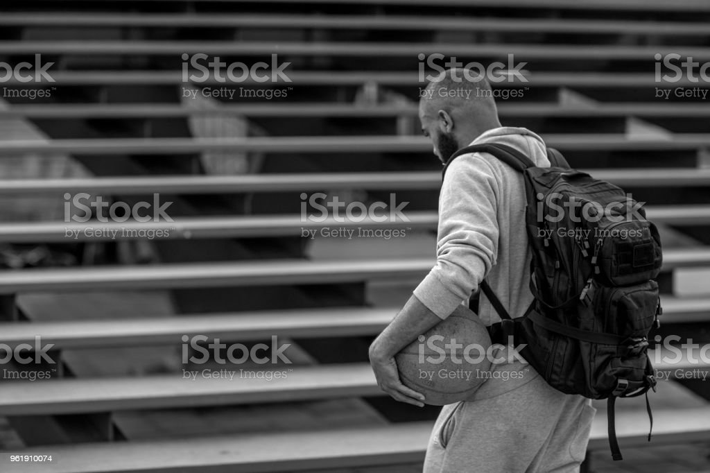 A young male basketball playing student sitting on some city steps stock photo
