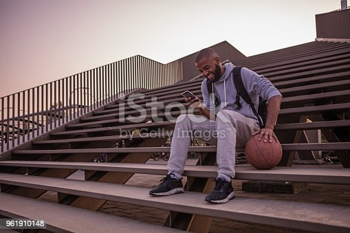 istock A young male basketball playing student using his smartphone whilst sitting on some city steps 961910148