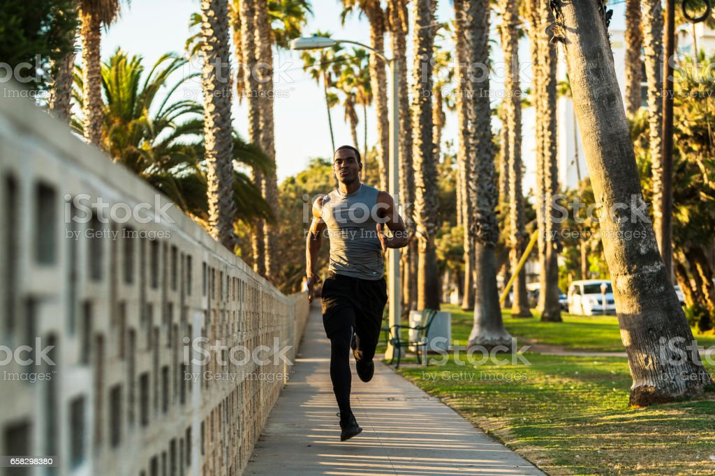 Young male black athlete exercising in the park, Los Angeles stock photo