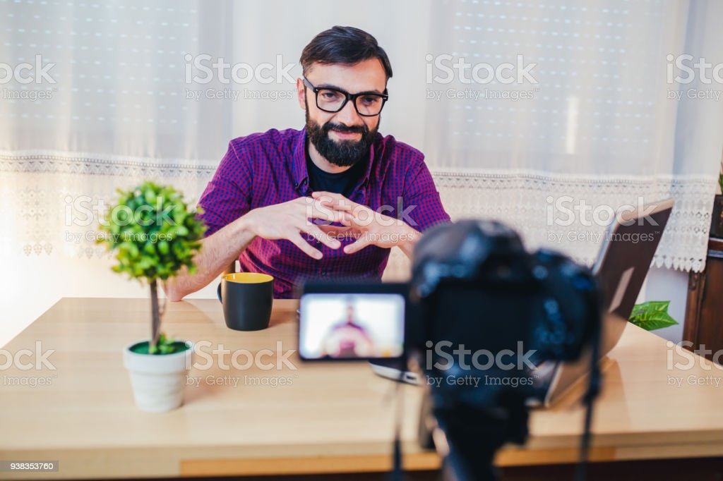Young male blogger recording video at home stock photo