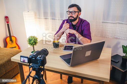 1179265329 istock photo Young male blogger recording video at home 938353844