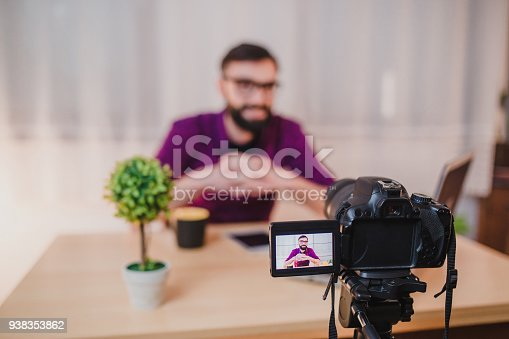 1179265329 istock photo Young male blogger recording video at home 938353862