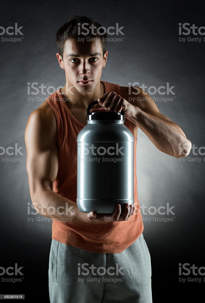 young male bodybuilder holding jar with protein stock photo