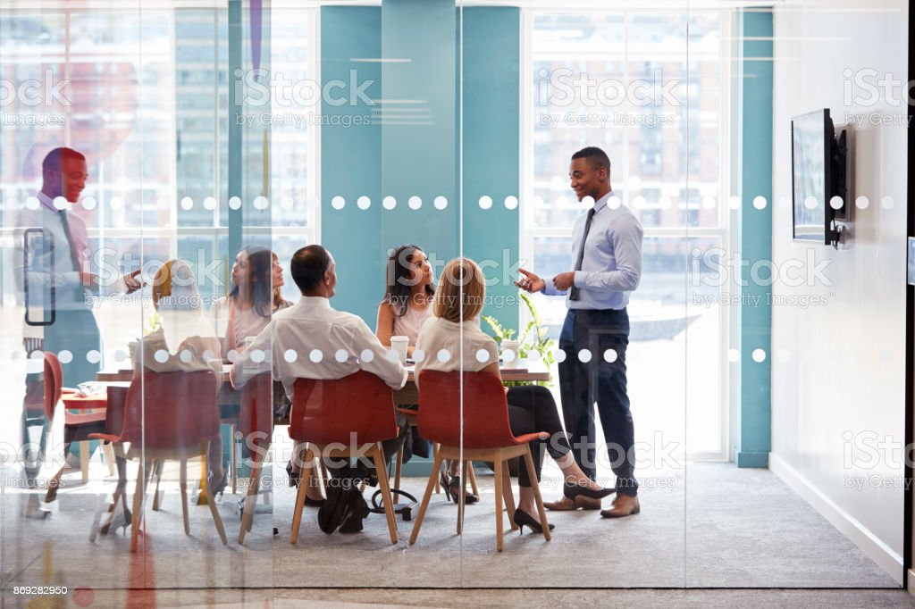 Young male boss stands addressing business team at meeting stock photo