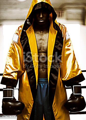 Young male boxer with boxing gloves and boxing robe waiting in boxing ring.