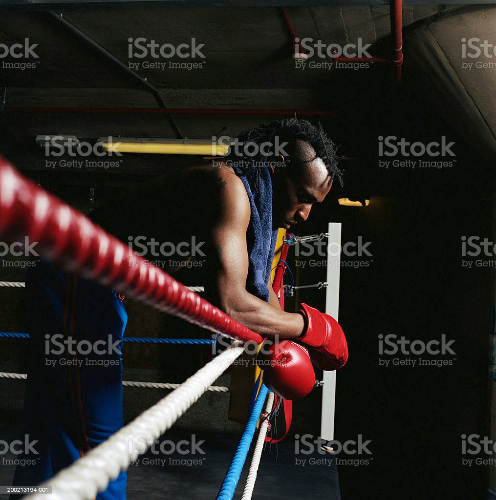 Young male boxer resting elbows on ring side, head bowed, side view