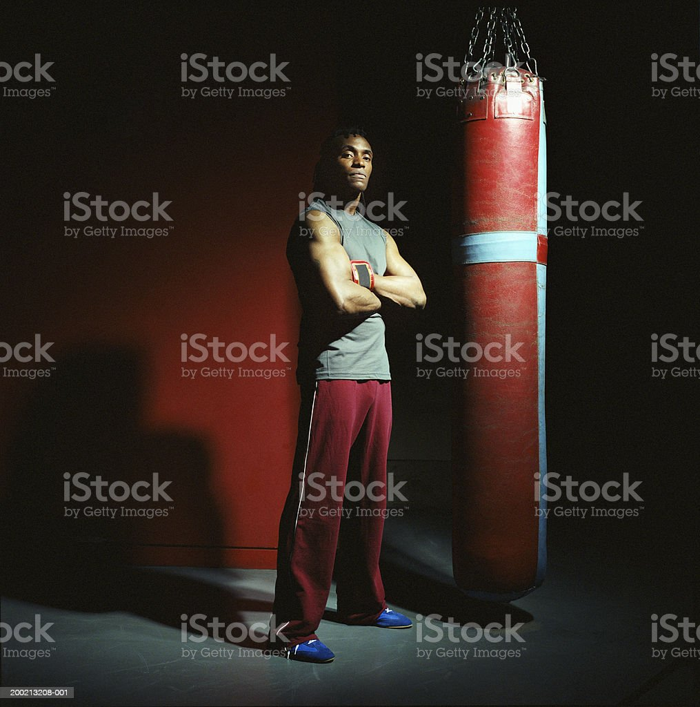Young male boxer standing by punch bag, arms crossed, portrait stock photo