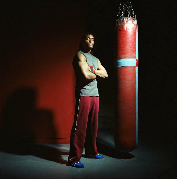 Joven boxeador macho con Este punzón bolsa, brazos cruzados, de retratos - foto de stock