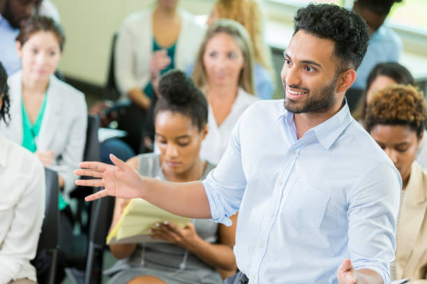Young male business graduate student lectures undergraduate students stock photo