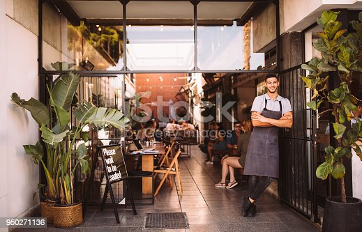 Young male manager and business owner standing at the entrance of modern urban restaurant
