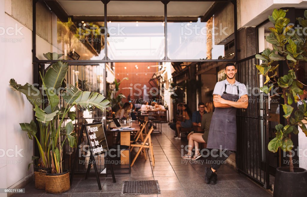 Young male business owner standing outside hipster urban café stock photo