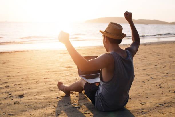 Junger Geschäftsmann, der am tropischen Sommerstrand die Hände für den Erfolg aufgibt-es zeigt Freiheit wie finanzielle Freiheit oder Fernarbeitskonzept – Foto